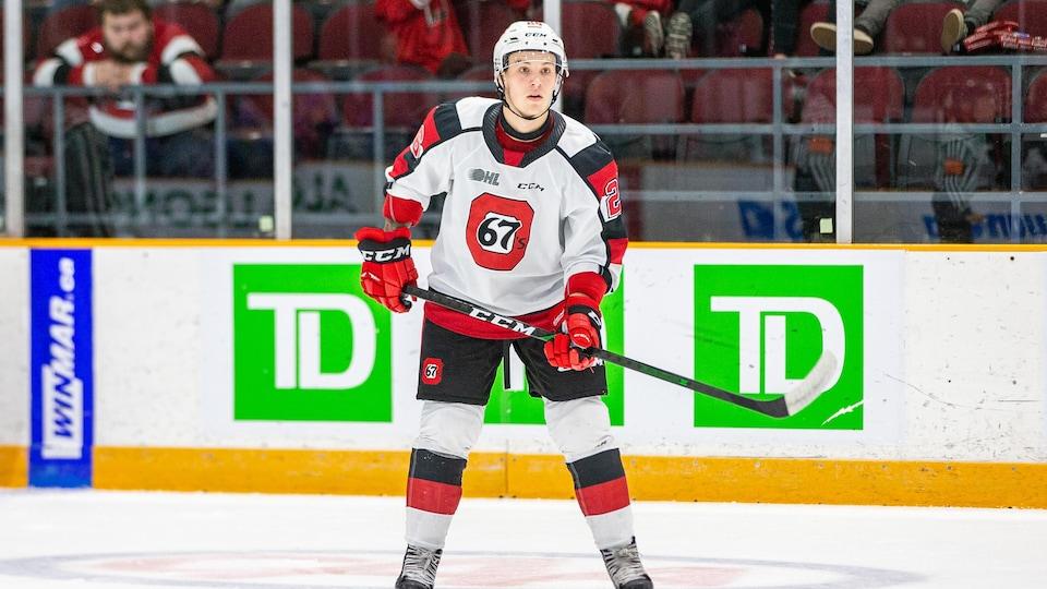 Un joueur de hockey regarde le jeu alors qu'il se trouve à l'extérieur de l'action.