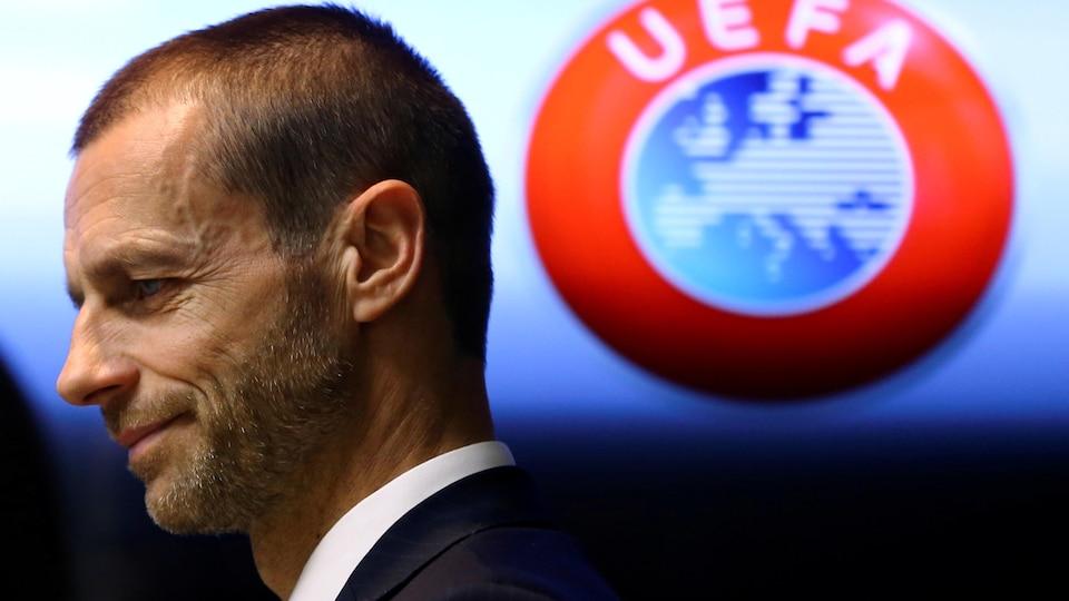 L'homme sourit timidement devant un logo de l'UEFA.