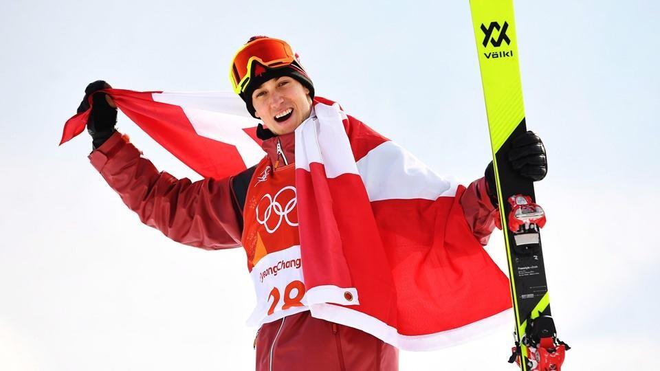 Alex Beaulieu-Marchand célèbre avec un drapeau canadien autour du cou.
