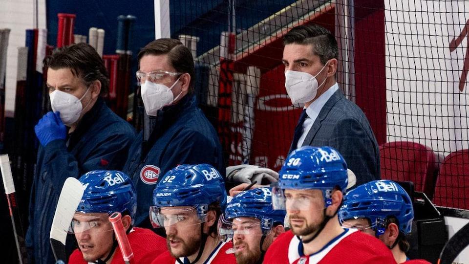 Alex Burrows, des membres du personnel et des joueurs du Canadien de Montréal regardent l'action.