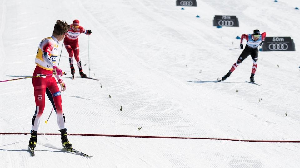 Johannes Klaebo regarde la bataille pour la 2e place entre Alex Harvey et Alexander Bolshunov dans la poursuite de 15 km à Québec.