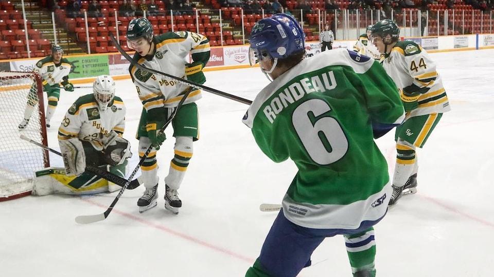 Du coin de la patinoire, Alex Rondeau tente un tir vers le gardien des Broncos de Humboldt.