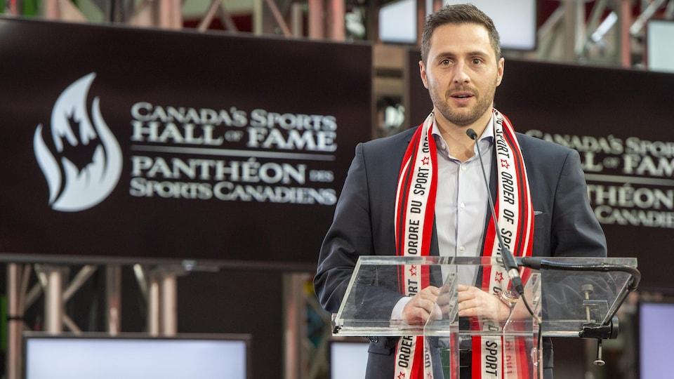 Un jeune homme en complet prononçant un discours au podium.