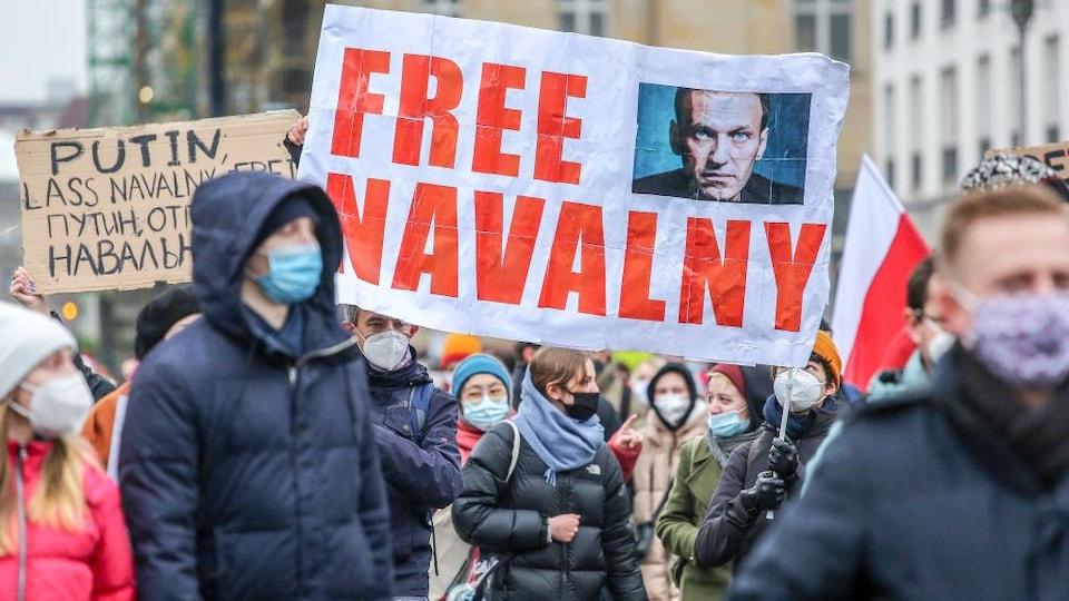 Des manifestants masqués portent des pancartes en faveur de Navalny et en opposition à Poutine.