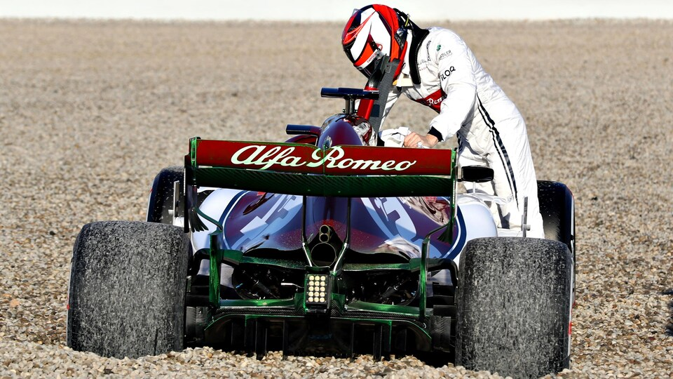 Il est debout à côté de sa monoplace Alfa Romeo après une sortie de piste sur le circuit de Barcelone.