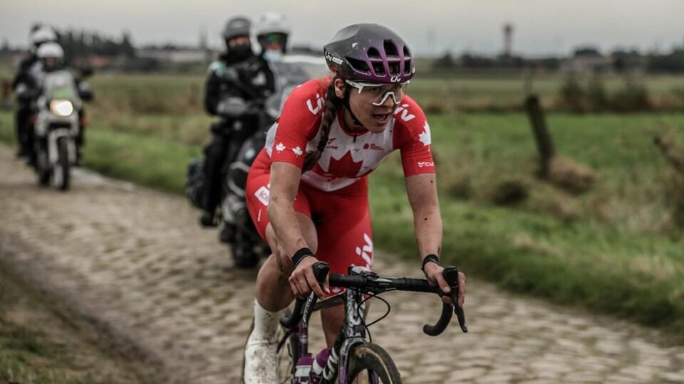 La cycliste sur son vélo négocie des secteur pavés.