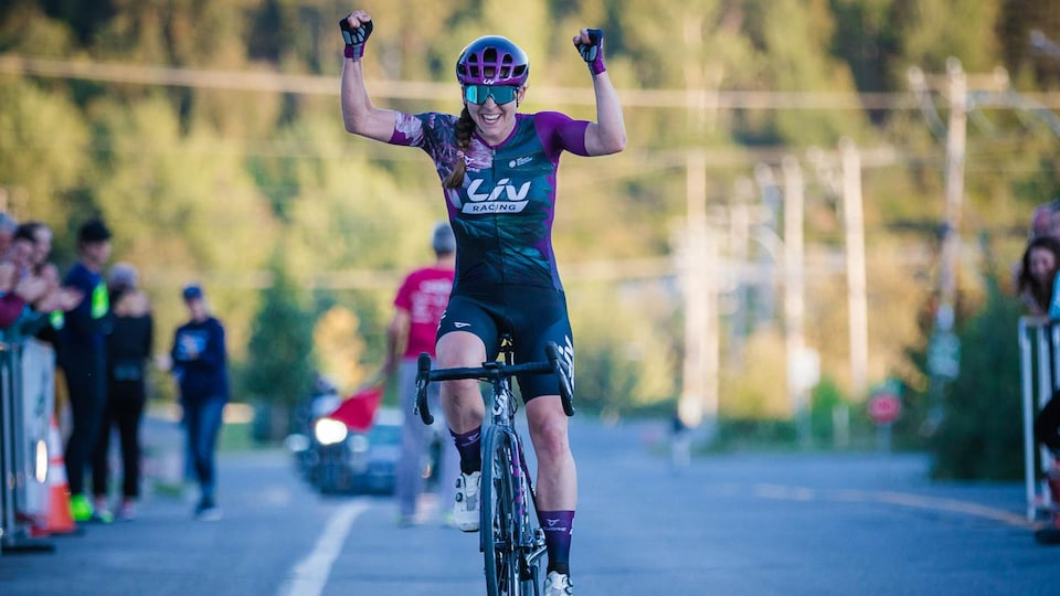 La cycliste célèbre sa victoire en levant les bras.