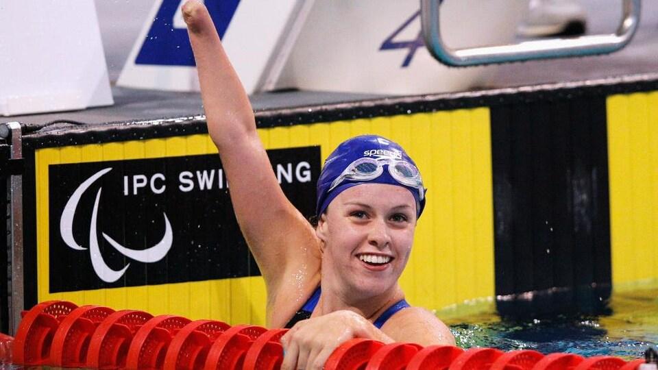 Amy Marren célèbre en soulevant son bras amputé, dans la piscine, après une victoire.