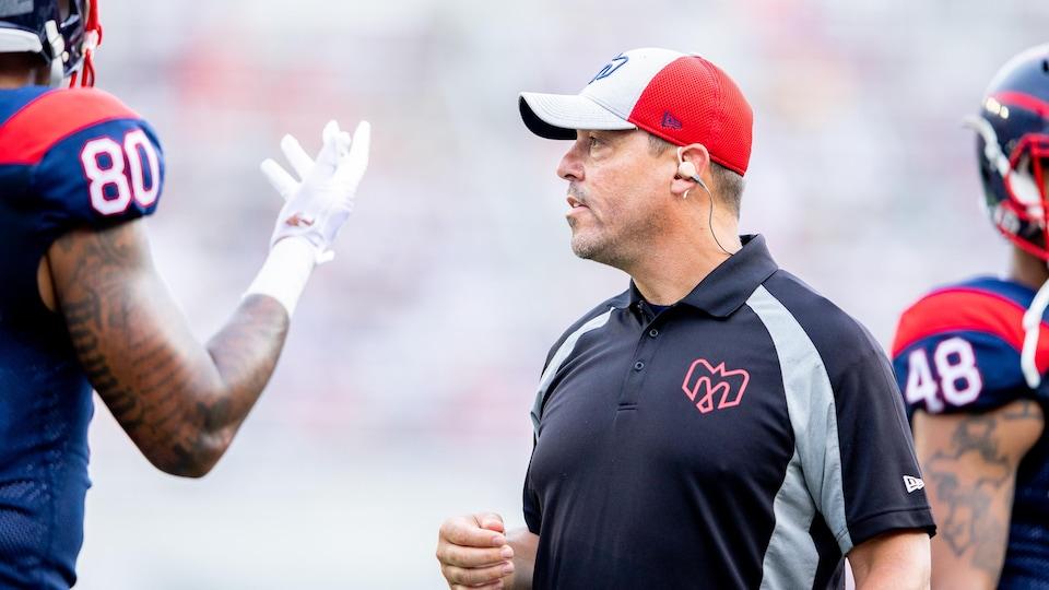 L'entraîneur donne des instructions à un joueur en bordure du terrain.