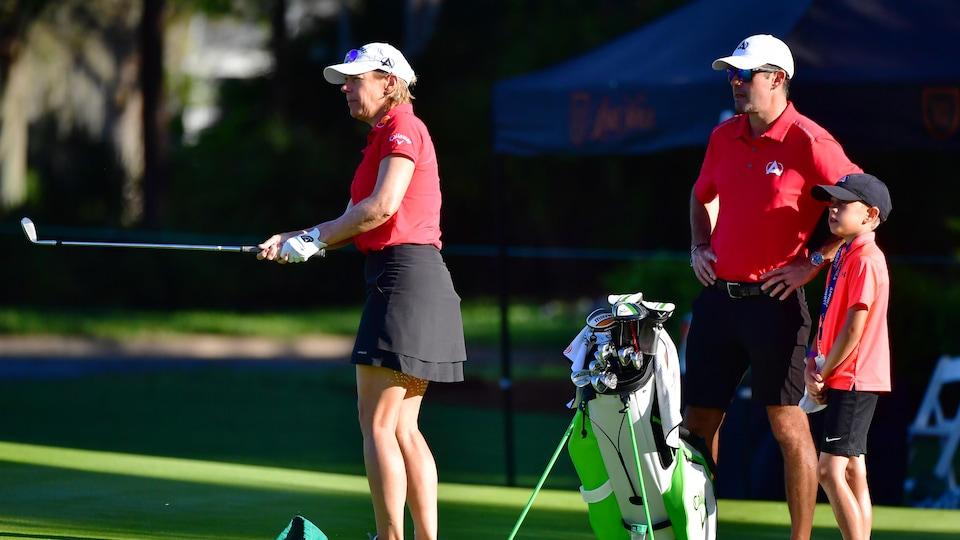 La golfeuse s'exerce devant son mari et son fils.