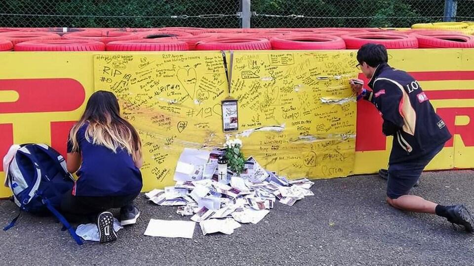 Les gens écrivent des messages pour Anthoine Hubert à l'endroit de son accident au circuit de Spa.