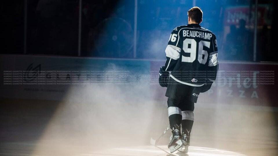 Anthony Beauchamp, de dos, s'amène sur la patinoire sous les projecteurs.