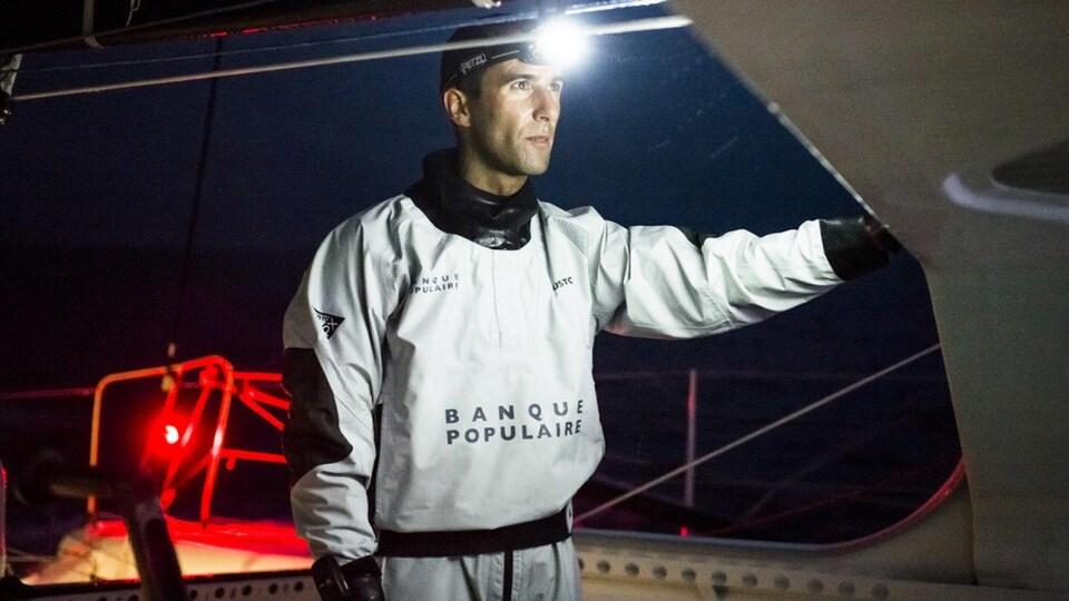 Un navigateur avec une lampe frontale la nuit, en mer