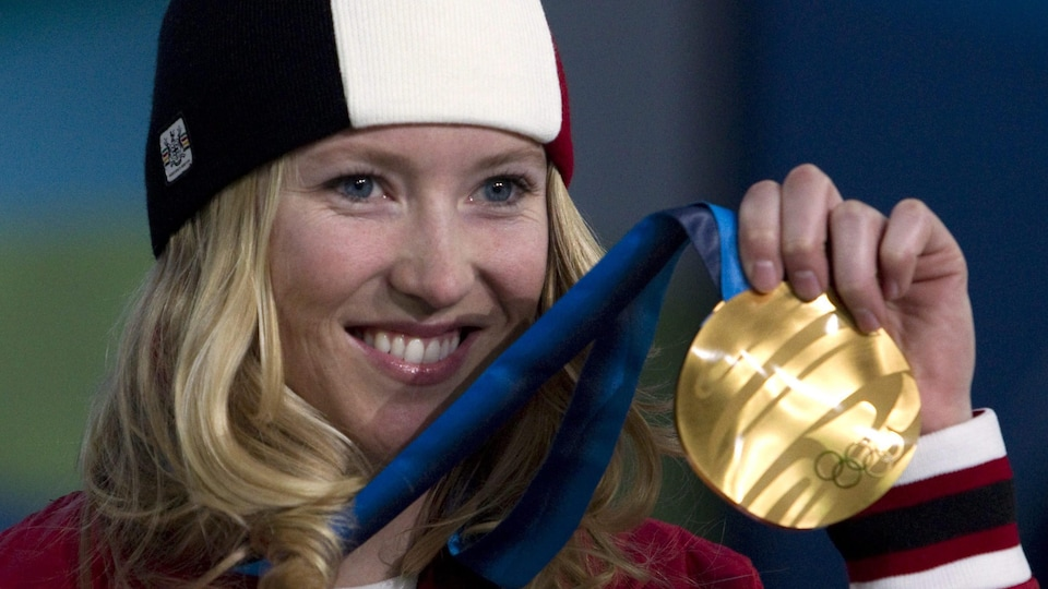 Elle est debout sur le podium et tient sa médaille d'or avec sa main gauche.