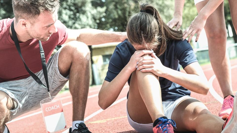 Une adolescente est assise au sol, elle se tient le genou. Un entraîneur la réconforte.