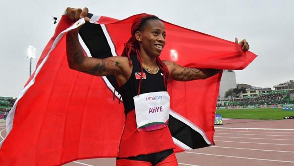 Elle fait un tour de piste avec le drapeau de son pays.