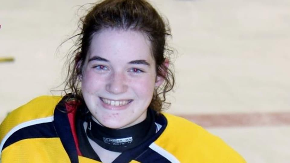Audrey Gdoin sourit en uniforme de hockey et porte un trophée.