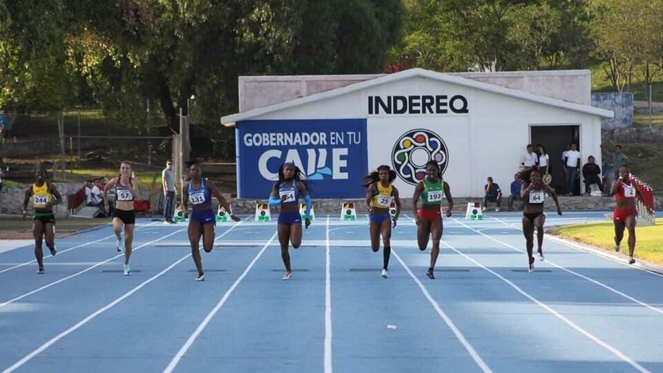 Huit femmes athlètes participent à une course de 100 mètres.
