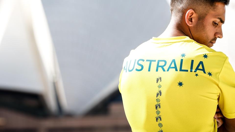 Il pose de dos et regarde de côté devant l'Opéra de Sydney.