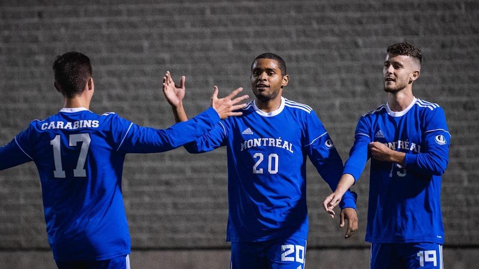 Trois joueurs de soccer vêtus de bleu célèbrent un but marqué par leur équipe.