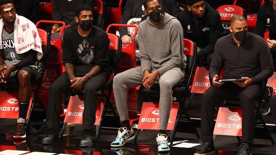Il est assis à côté de son coéquipier Kevin Durant au banc. Ils portent un masque.