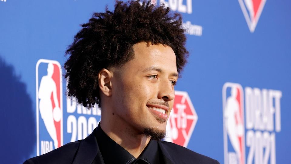 Le basketteur est devant un mur bleu.