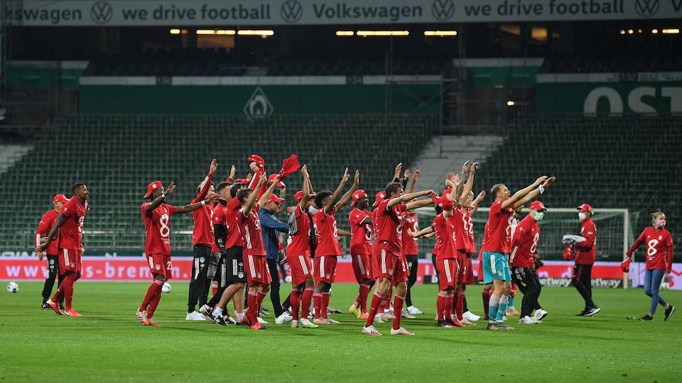 Les joueurs du Bayern fêtent, dans un stade vide, sous la pluie.