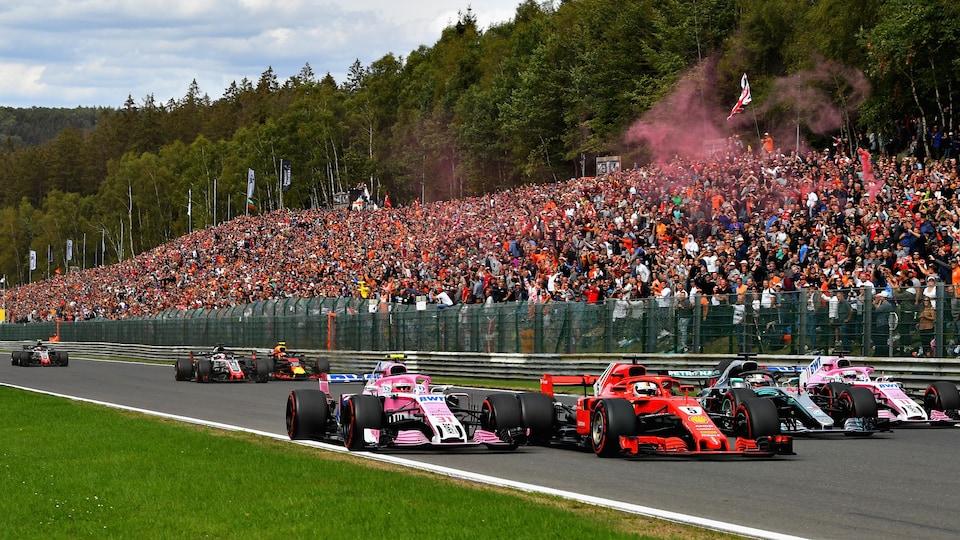 Esteban Ocon (à gauche) attaque Sebastian Vettel (en rouge), tandis que Sergio Pérez (à droite) attaque Lewis Hamilton (en gris) sur le circuit de Spa-Francorchamps.