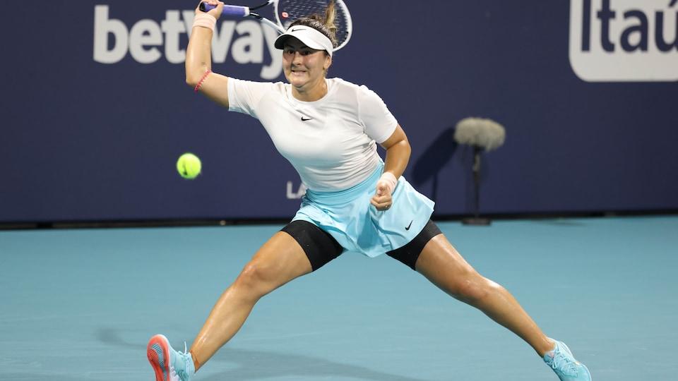 La joueuse de tennis plonge à sa droite pour frapper la balle.