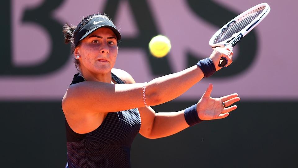 Une joueuse de tennis vêtue de noir s'apprête à frapper une balle du revers.