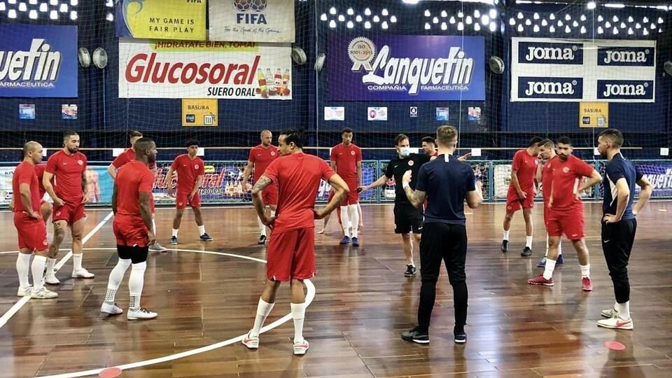 Des joueurs de futsal, réunis en cercle, écoutent les consignes de l'entraîneur pendant une pratique.