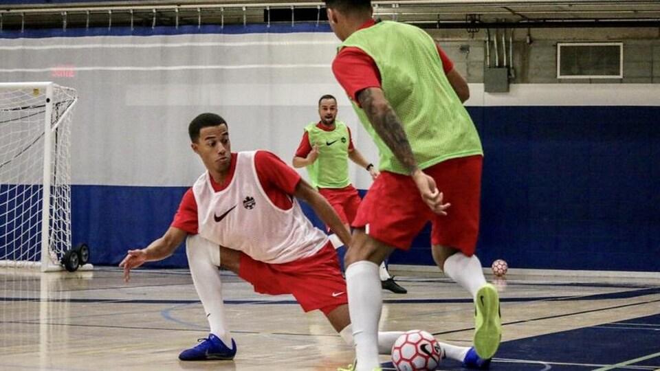 Un joueur de futsal est agenouillé devant un adversaire lors d'un entraînement.