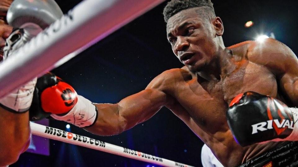 Il se jette sur son adversaire, coincé dans le coin du ring.