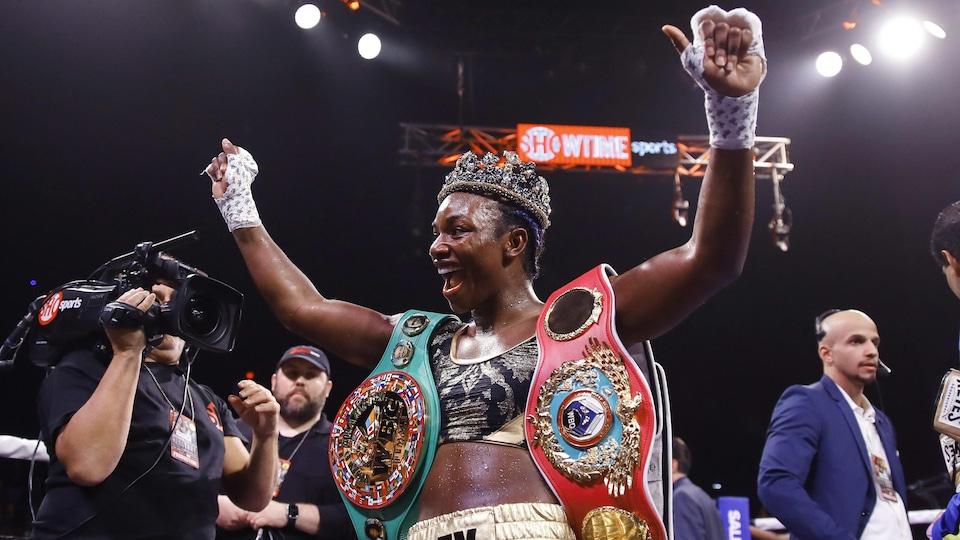 Une boxeuse pose avec ses ceintures de championne.