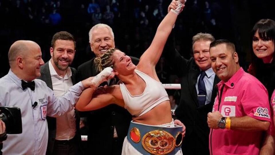Une boxeuse fait une pose triomphante.