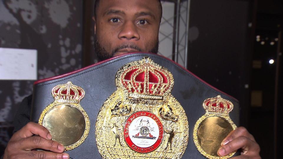 Il montre sa ceinture des mi-lourds de la WBA.
