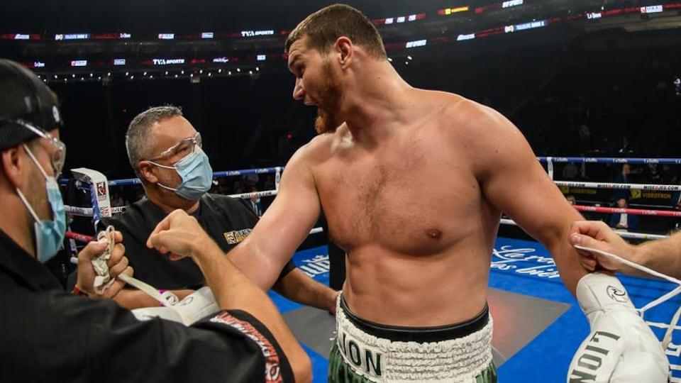 Un entraîneur de boxe félicite son protégé dans le ring après une victoire.