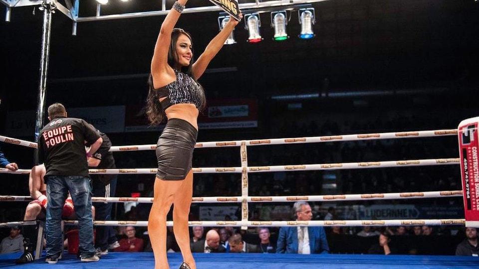Une femme avec sa pancarte au centre du ring