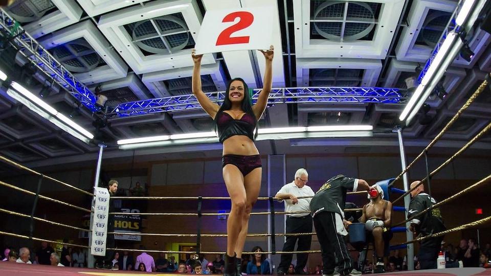 Une jeune femme avec une pancarte dans un ring