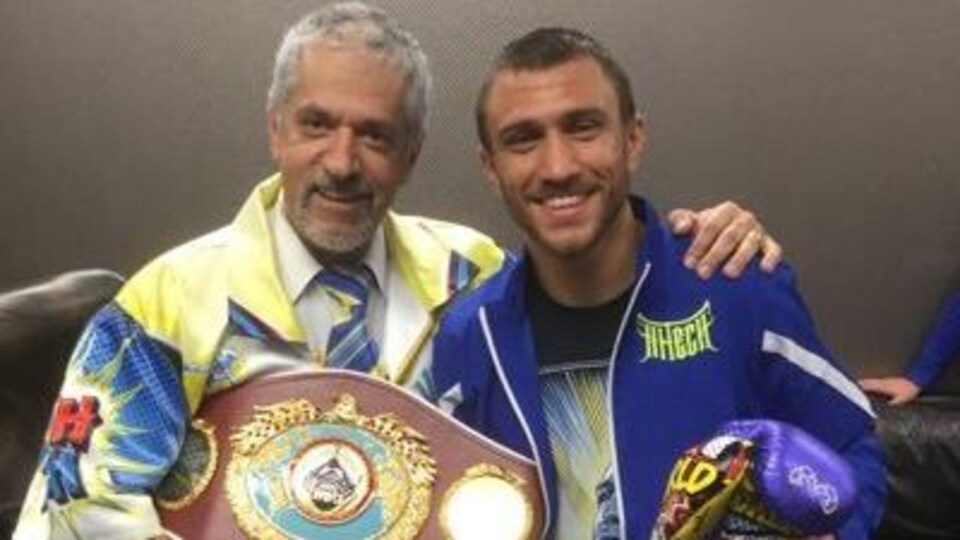Ils sourient en tenant une ceinture de champion.
