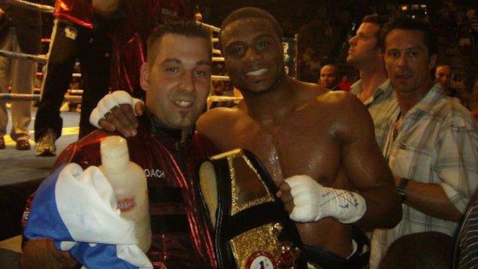 Un entraîneur et un boxeur posent avec une ceinture.