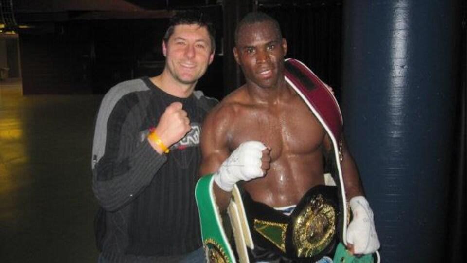 Il prend la pose avec un boxeur qui tient une ceinture.