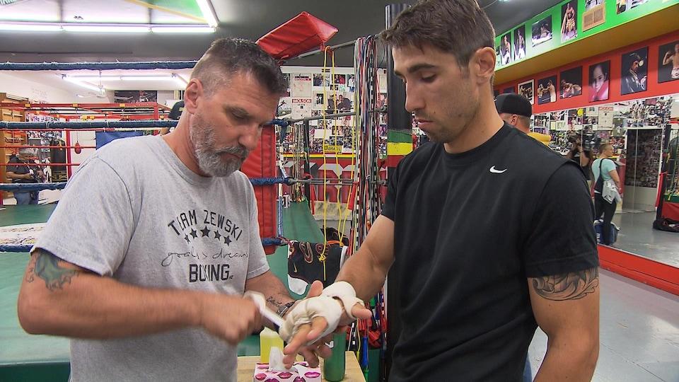 Jean Zewski, père et entraîneur, appose le ruban sur les mains de son fils.
