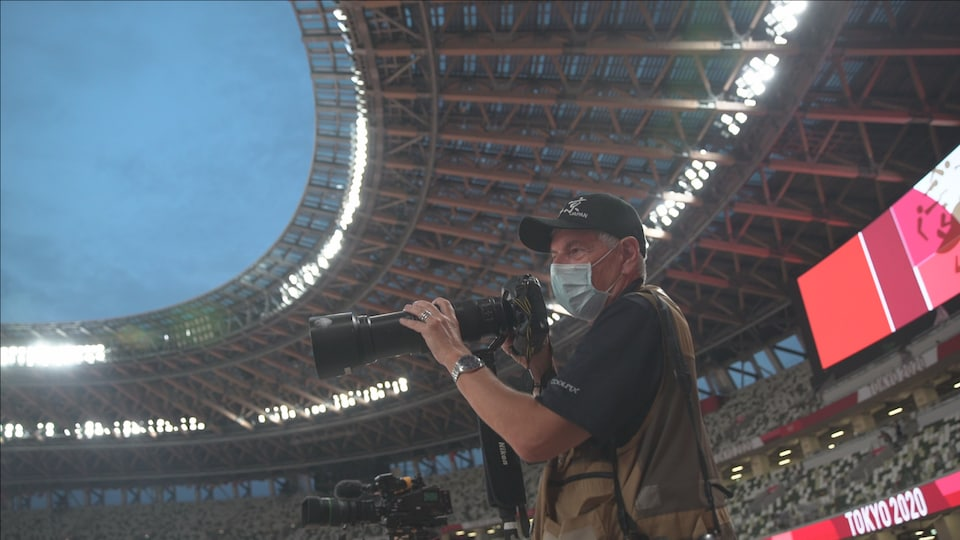 Le photographe Bernard Brault porte un masque derrière son appareil photo.