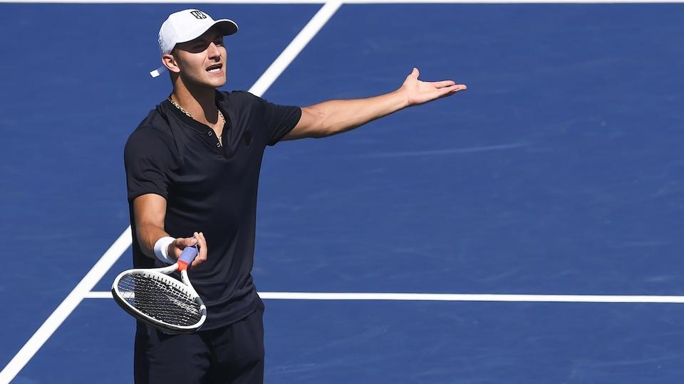 Un joueur de tennis vêtu d'un polo bleu et d'une casquette blanche ouvre les bras avec sa raquette et semble frustré par la tournure des événements.