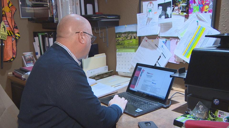 Brent Parker en train de consulter un rapport de dépistage dans son bureau, situé dans le sous-sol de sa maison.