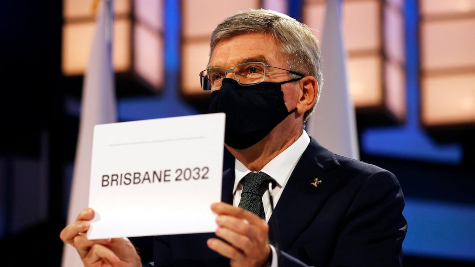 Il présente un carton sur lequel il est écrit Brisbane 2032.