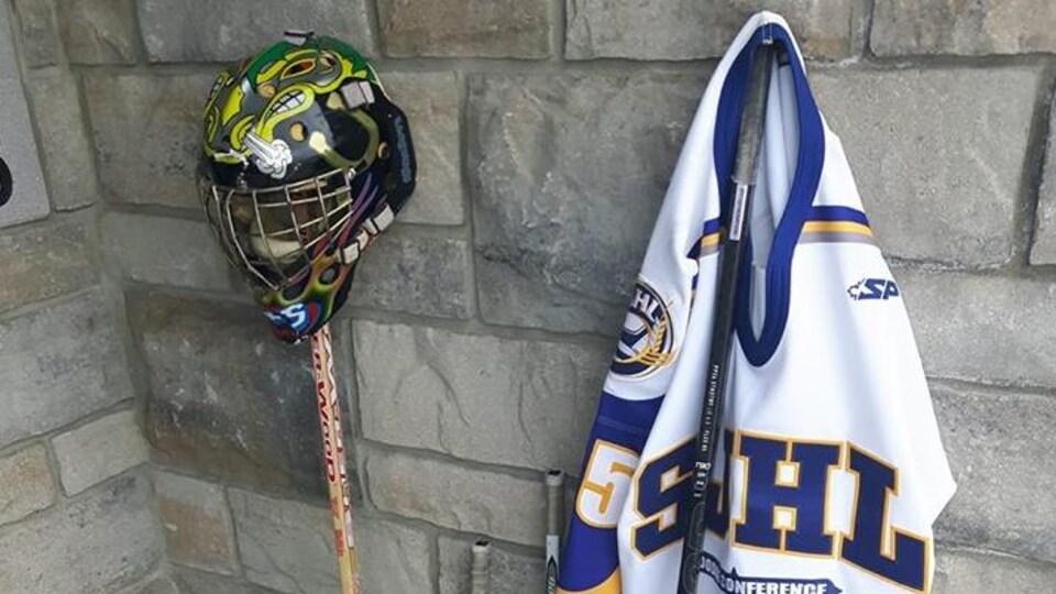 Quatre bâtons de hockey, un masque de gardien et un chandail sont placés à l'extérieur de la maison d'Alex Gagnon.
