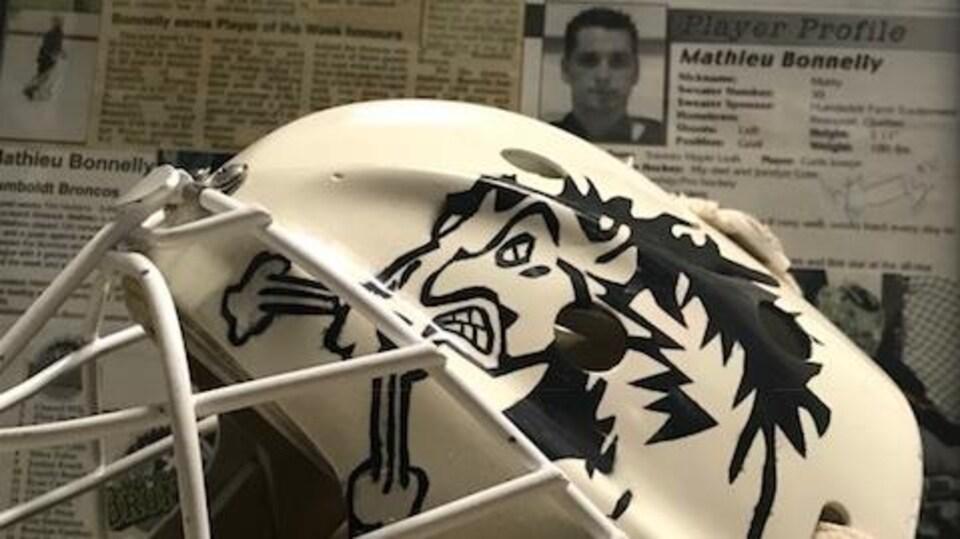 Un masque de hockey devant des coupures de journaux relatant le passage du gardien à Humboldt.