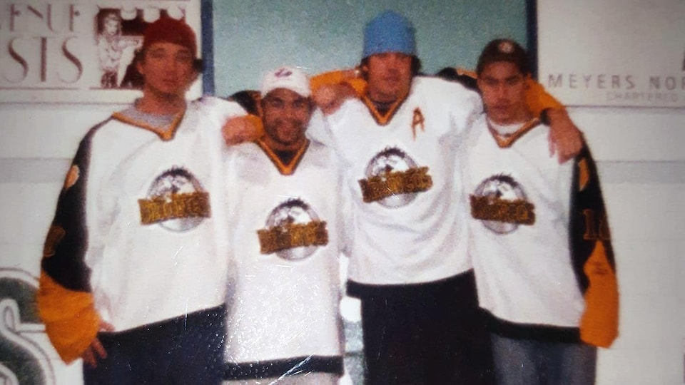 Les quatre hockeyeurs québécois posent sur le banc des joueurs.